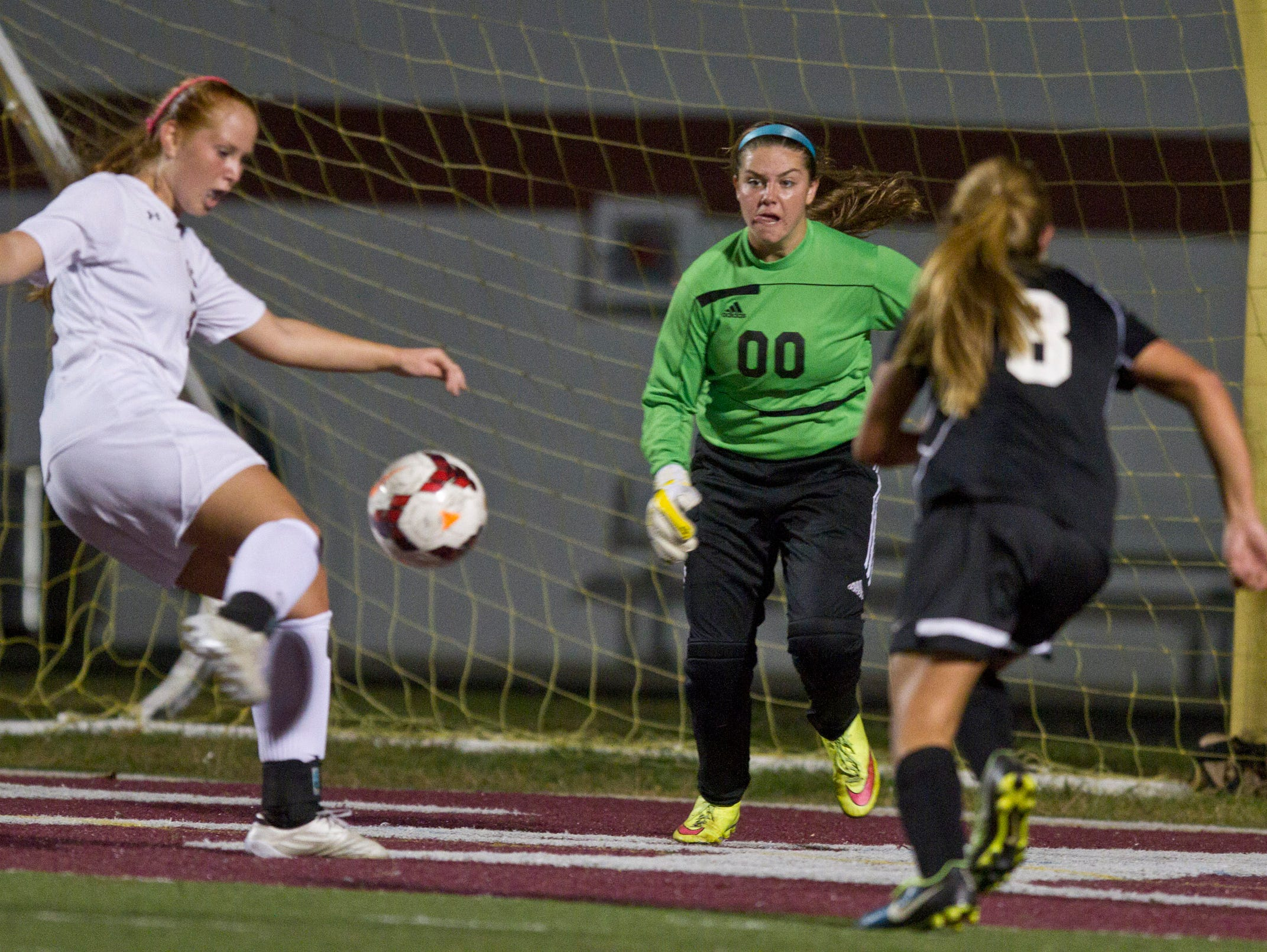 Toms River East goal keep Jordyn Ferone defends as Toms River South's Katie Hammack puts a shot on goal. Toms River East vs Toms River South soccer. Toms River, NJ Tuesday, October 13, 2015 @dhoodhood