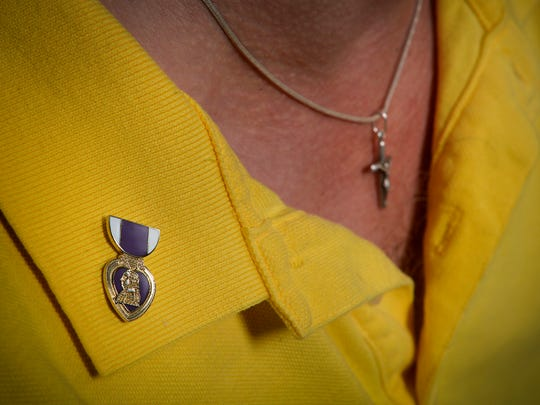 Freeport veteran Mike Mills wears a Purple Heart pin as he talks Thursday, Dec. 10 about the 56 surgeries he's endured after he nearly lost his life from his wounds in Iraq in 2005. Now, he's started an organization that helps other combat-wounded vets.