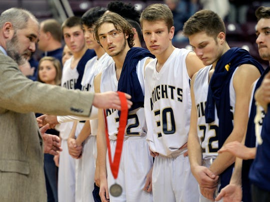 Eastern York boys' basketball players watch as teammates receive the runner-up medals  Thursday.