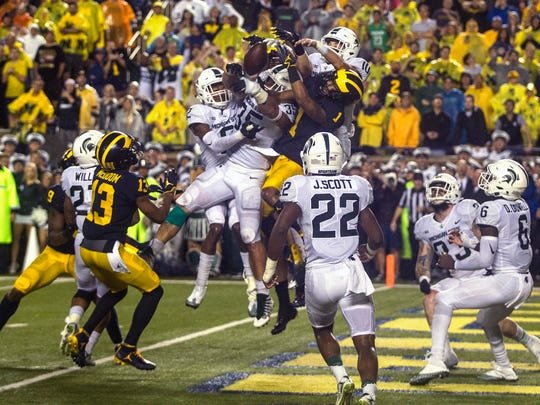 Michigan State LB Joe Bachie (35) and teammates break up a pass-attempt intended for Michigan WR Kekoa Crawford (1) in the final seconds of the MSU and U-M game at Michigan Stadium in Ann Arbor on Sat., Oct. 7, 2017.