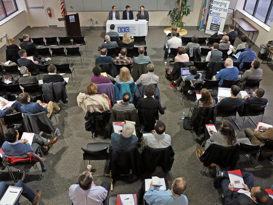 More than 100 attendees listen to a panel of former