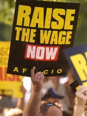 A supporter of raising the minimum wage waves a sign during Claire McCaskill's speach at the Labor Day picnic in 2014.