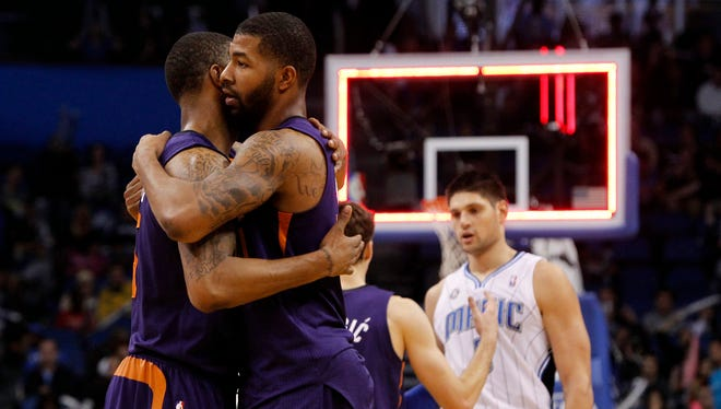 Suns power forward Markieff Morris (11) and power forward Marcus Morris (15) hug after they beat the Orlando Magic during the second half at Amway Center.