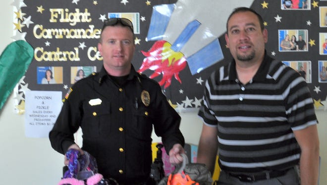 Silver City Police Department Lieutenant James Cruzan helped distribute coats to Harrison Schmitt Elementary School. Counselor Chris Sedillo helped receive them.