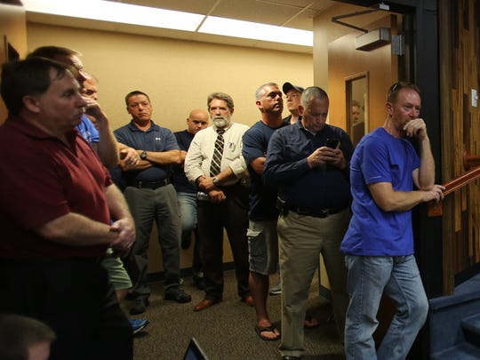 Police officers listen as people speak to support suspended Police Chief Sullivan in a packed hearing room during Clarkstown Town Board meeting in New City Aug. 9, 2016.