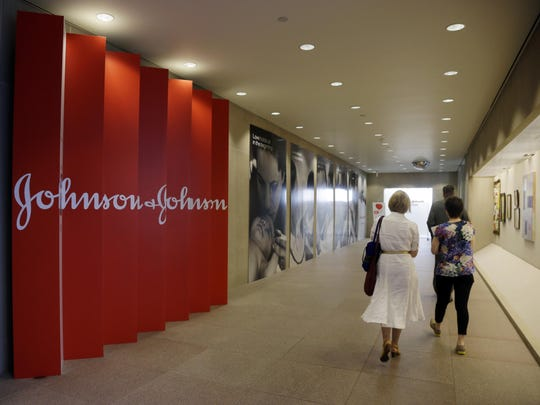 FILE - In this July 30, 2013, file photo, people walk along a corridor at the headquarters of Johnson & Johnson in New Brunswick, N.J.