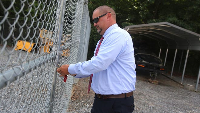 Cleveland County Schools Transportation Director David Pless opens the gate to the seized car lot on Thursday. Seized cars are auctioned off to benefit the Cleveland County Schools transportation department.