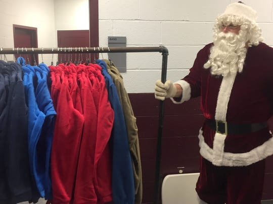 Santa, known to some by his nickname Jack Hancock, helps move a bunch of brand new Columbia jackets waiting to be given to kids at Sunday's Goodfellows Christmas party.