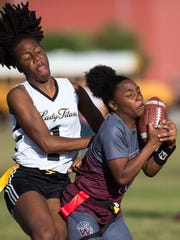 Fort Pierce Westwood's Lawayndra Walker makes a reception in the third quarter as Treasure Coast's Jessica Nerestant defends during the high school flag football game Thursday, March 8, 2018, at Treasure Coast High School in Port St. Lucie.