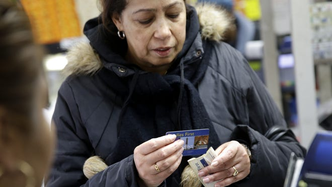 A woman pays for her groceries using a food stamp program at a supermarket.