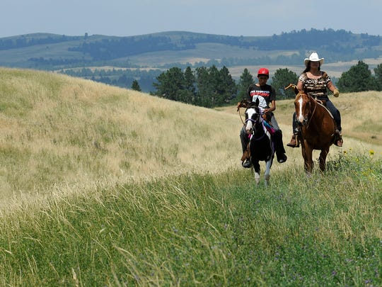 Charles Marshall, 14, and Mae Rodriguez ride horse past Wounded Knee into Pine Ridge, S.D. on Thursday, August 1, 2013.
