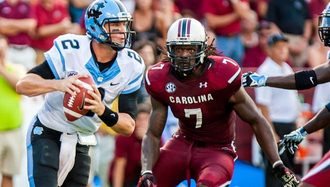 North Carolina quarterback Bryn Renner (2) scrambles as he is pursued by South Carolina defensive end Jadeveon Clowney (7) in the second quarter at Williams-Brice Stadium on Thursday.