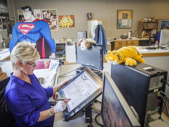 Paws, Inc. comic strip inker Lori Barker works at her desk in Albany.