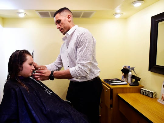 Teddy Cravens cuts the hair of Kalyn Goodrich, 10, at Iridescence Salon and Spa in Springettsbury Township. Cravens' driving goal is to help his clients, at the salon and the gym, to be the best version of themselves.