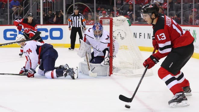 Devils center Nico Hischier (13) plays the puck to the side of the net of Washington Capitals goalie Vitek Vanecek (41) during the second period at Prudential Center during a preseason game on Sept. 18, 2017.