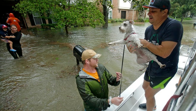 Volunteers evacuate people and pets from a neighborhood inundated by floodwaters from Tropical Storm Harvey on Monday, Aug. 28, 2017, in Houston, Texas.
