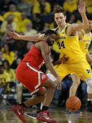 Michigan forward Mark Donnal defends against Ohio State guard JaQuan Lyle during the first half of U-M's 70-66 loss Saturday at Crisler Center.