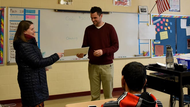 Megan Evans presents Licking Heights High School teacher Sean McCullough with a travel grant from the Licking County Foundation. The Tibbie Leslie Travel Grants are awarded to teachers who plan foreign travel to broaden their experience and knowledge in their particular field.
