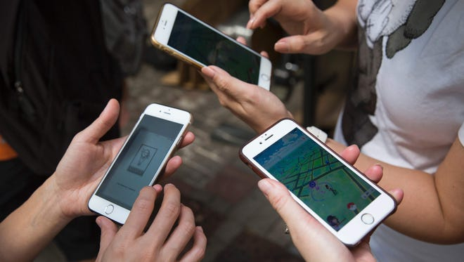 Participants use their smartphones as they play the gaming app Pokemon Go.