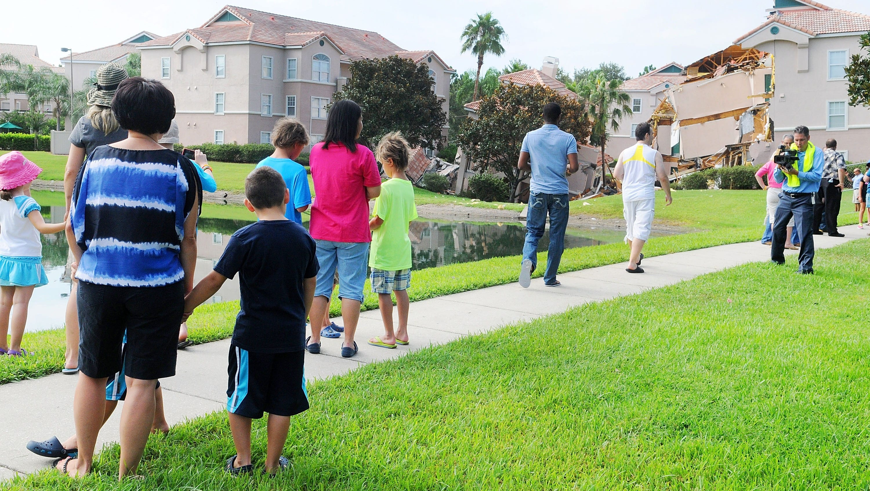 People stand near a partially collapsed building at Summer Bay Resort in Clermont, Fla. Engineers on Aug. 12 were trying to determine the extent of the damage  after luxury resort condominiums crumbled into a massive sinkhole.