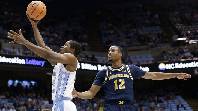North Carolina's Kenny Williams drives to the basket while Michigan's Muhammad-Ali Abdur-Rahkman (12) defends during the first half on Wednesday, Nov. 29, 2017, in Chapel Hill, N.C.