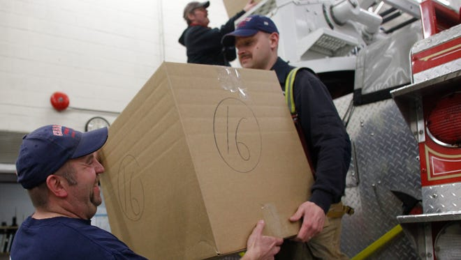 Volunteer fireman Corey Sander, left, of Charlotte, helps load a fire truck with Christmas presents on Christmas Eve 2014.
