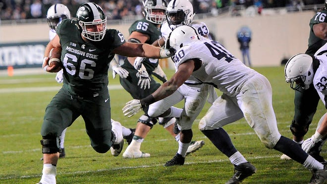 Center Jack Allen (66) stiff arms a Penn State defender on his way to a nine-yard touchdown run in the second half of MSU's 55-16 win over Penn State Saturday, November 28, 2015, at Spartan Stadium in East Lansing.