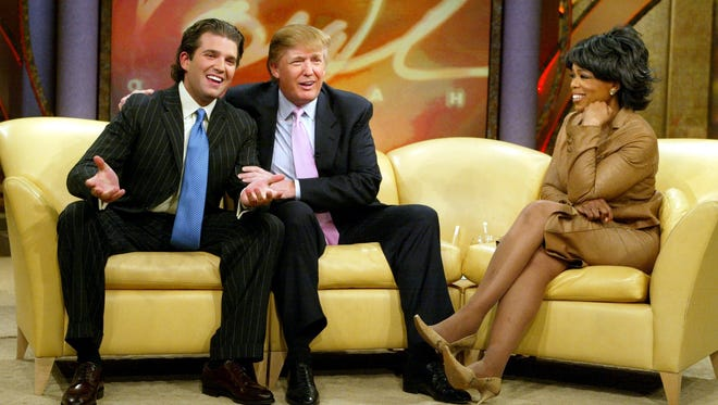 """Oprah Winfrey is joined by Donald Trump and Donald Trump Jr., left, during a taping for the """"Oprah Winfrey Show"""" in February 2004, in Chicago."""