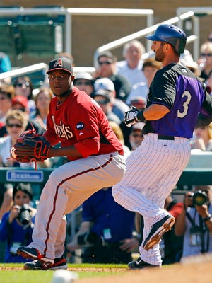 Diamondbacks pitcher Rubby De La Rosa (left) gets an out at first base against the Rockies shortstop Daniel Descalso on Wednesday, March 4, 2015, at Salt River Fields at Talking Stick.