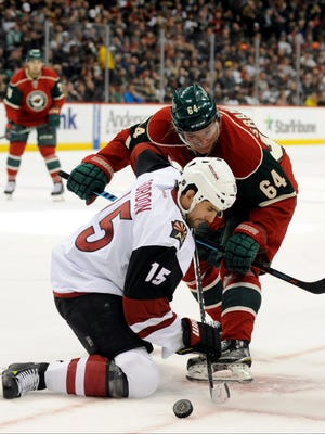 Jan 25, 2016: Arizona Coyotes forward Boyd Gordon (15) wins the face off against Minnesota Wild center Mikael Granlund (64) during the second period at Xcel Energy Center.