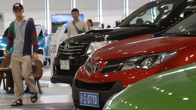 Visitors looks at cars displayed at a Toyota gallery in Tokyo, May 8, 2014.