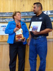 Ruidoso Village Manager Debi Lee holds the traveling bear award while Issac Garcia, who heads the Regional Wastewater Treament Plant accepts a plaque for Department of the Quater. He received the public works employee of the quarter award earlier.