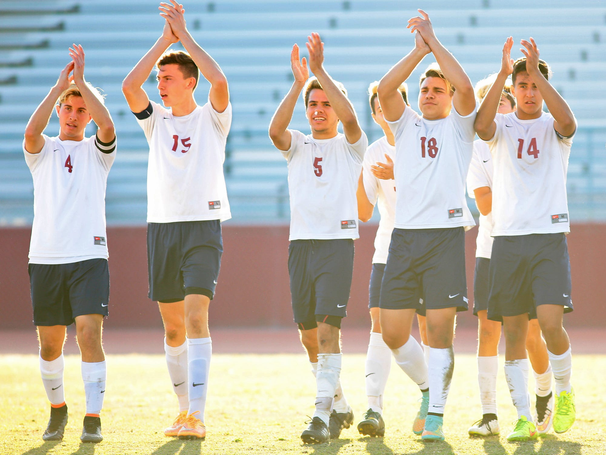 La Quinta players senior Isaac Sanchez (4), junior Daniel Alexander (15), senior Jesus Avalos (5), senior Aaron Mendoza (18), and junior Alexis Vargas (14) turn toward the crowd and clap while celebrating the Blackhawks' 1-0 win in a CIF semifinal playoff game Tuesday afternoon at home against Sunny Hills.