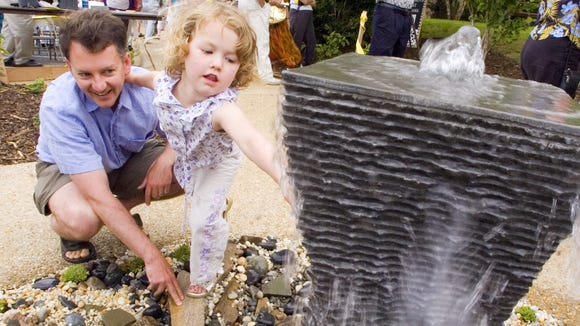 Jim Josefson of Stuarts Draft holds onto his daughter, Clair Josefson, 4, as she reaches out to touch the water of a fountain following the dedication ceremony for the Brenda Lee Papke Memorial Sensory Garden outside the Staunton Public Library on Tuesday, May 22, 2007.