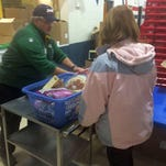 Doug Siebert, right, an elder at Redeemer Lutheran Church in Green Bay, helps Mary Shearer select food items from the first Ruby's Pantry distribution at the church Monday night.