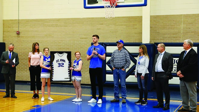 Taking part in a special jersey retirement ceremony honoring St. John alumni and basketball standout Dean Wade (middle) on Friday were (from left) USD 350 Superintendent Josh Meyer, Trish Wade, cheerleaders Whitney Brummer and Lexie Brummer, Dean Wade, Jay Wade, Sara Fisher, Clint Kinnamon and Blaine White.