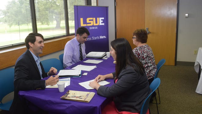 Patton Griffith (left, front), director of continuing education at LSU of Eunice, talks with attorney Meagan Miller (front, right) at an adjunct faculty job fair June 30 at the Learning Center for Rapides Parish located on England Airpark. Several local colleges and universities were recruiting people to teach courses.