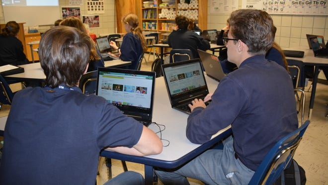 Students at St. Thomas More Catholic High School participate in the Hour of Code on Wednesday.