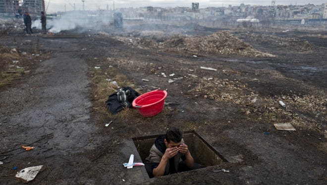 An Afghan refugee youth washes himself in a hole in the ground outside an old train carriage where he and other migrants took refuge in Belgrade, Serbia, Thursday, Feb. 2, 2017. Hundreds of migrants have been sleeping rough in freezing conditions in central Belgrade looking for ways to cross the heavily guarded EU borders.