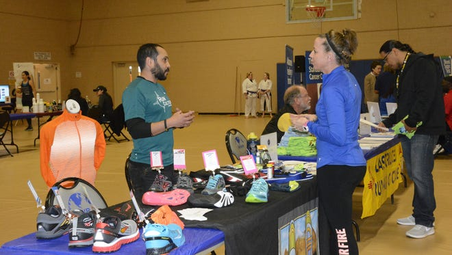 Carlos Rivas from Run Culture talks about finding the proper shoes to run in with Laura Justus during the first Health and Wellness Expo, Feb. 15. The expo vendors ranged from fitness centers, run groups and healthy grocery stores.