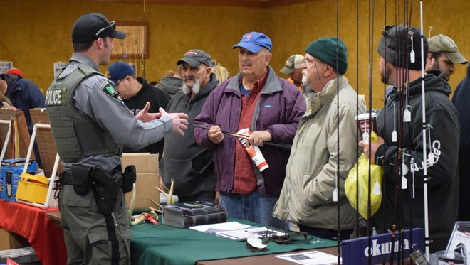 NJ Fish and Wildlife Conservation Officer Keith Fox talks with visitors Pasquale Nocito of Vineland, Leon Nocito of Millville and Bill Seeman of Mullica Hill during the South Jersey Bass Club Association's annual fisherman's flea market on Saturday, March 4.