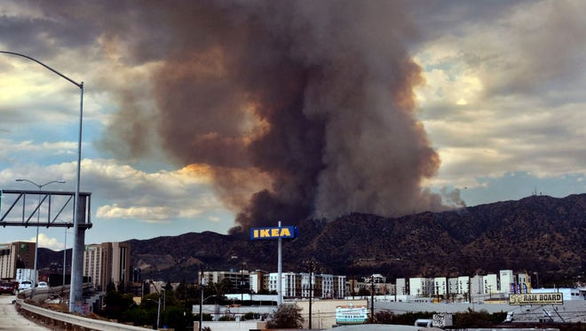 Heavy black smoke rises as a wildfire burns in Los Angeles.