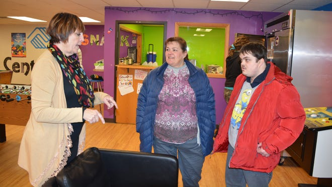 Judy Dobbins, Turning Point president and CEO, discusses programs available with Cindy Josefson and her son, Eric.