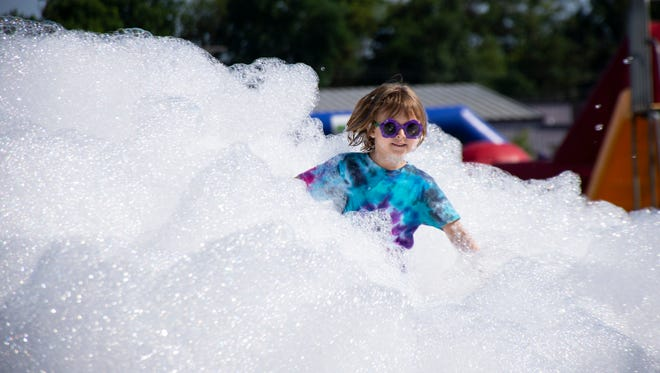 Ava Manry, 6 years of age, runs through the foam bubble at The Great Inflatable Race in Shrewsbury, Pa. on Saturday, July 14, 2018.