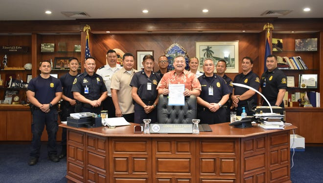 Gov. Eddie Calvo with Custom and Quarantine Agency officials signs a bill into law that reserves four acres of land for the construction of a new a Customs inspection, holding, and secured facility.