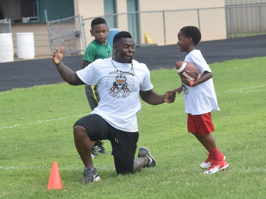 Jalen Richard of the Oakland Raiders, and a former Peabody Magnet High School football player, is impressed with the way Connor Benoit, 8 (right) evaded a tackle while doing a drill during the Jalen Richard Youth Football Skills Camp held Saturday at Peabody. Richard held two free football camps for children ages 8-12 and a second one for high school students. Richard hopes to make this an annual event.
