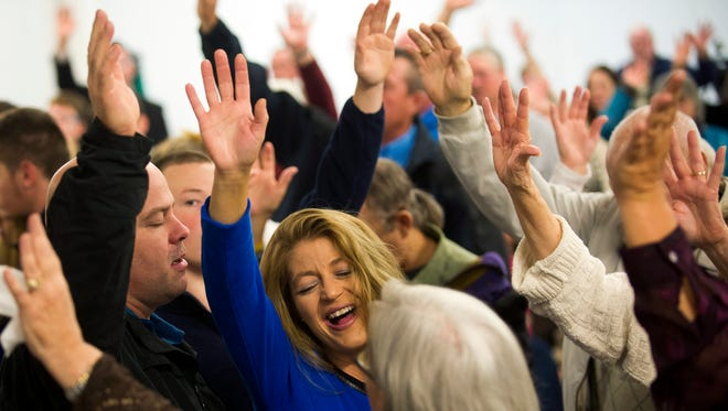 Roaring Fork Baptist Church congregants raise their hands together in praise during a Sunday morning service at Camp Smoky in Sevierville on Sunday, Dec. 4, 2016. Roaring Fork Baptist Church was destroyed in the fire that swept through Gatlinburg on Monday night.