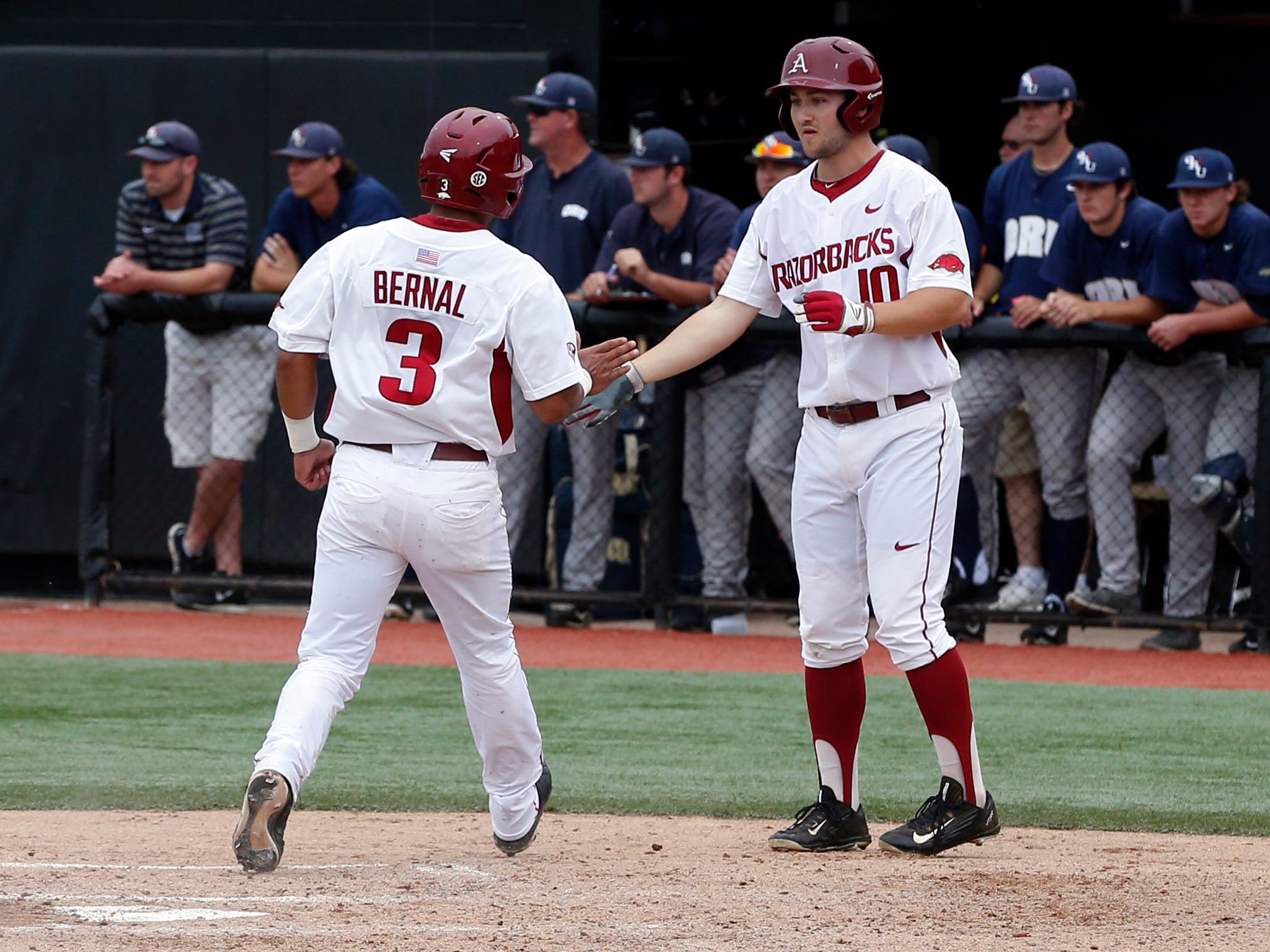 Arkansas's Michael Bernal (3) is congratulated by Joe Serrano (10) after Bernal scored off a single by Tucker Pennell against Oral Roberts in the third inning of a game at the Stillwater Regional of the NCAA college baseball tournament in Stillwater, Okla., Friday, May 29, 2015. (AP Photo/Sue Ogrocki)
