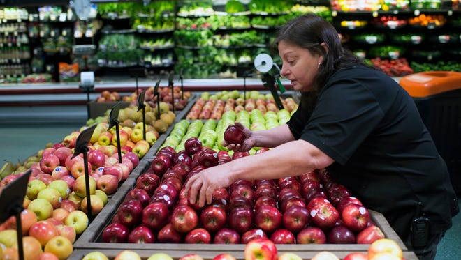 Produce manager Debbie Green culls apples for a food bank donation at ShopRite in Hammonton, N.J.