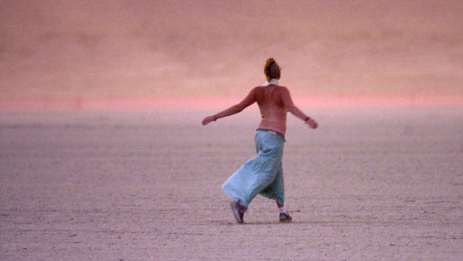 A participant at Burning Man delights in the rain following an afternoon sand storm on the playa in 2002.